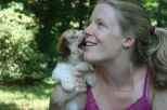 sable and white havanese puppies giving kisses to girls